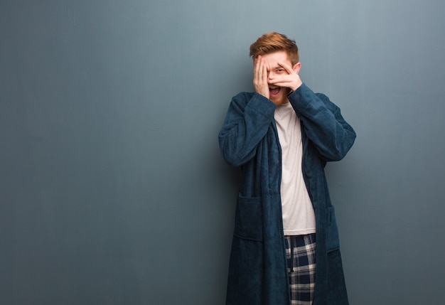 Young redhead man in pajama feels worried and scared