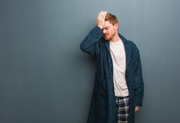 Young redhead man in pajama forgetful, realize something