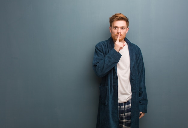 Young redhead man in pajama keeping a secret or asking for silence