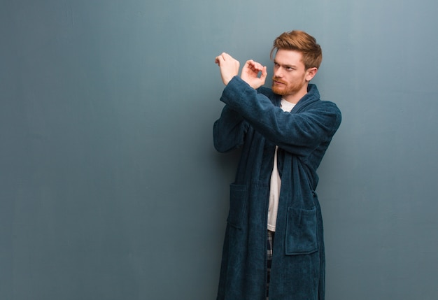 Young redhead man in pajama making the gesture of a spyglass