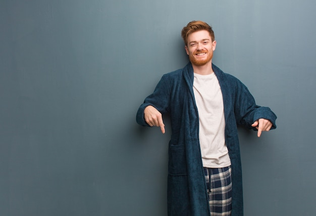 Young redhead man in pajama pointing to the bottom with fingers