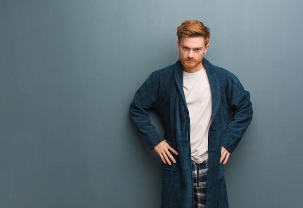 Young redhead man in pajama scolding someone very angry