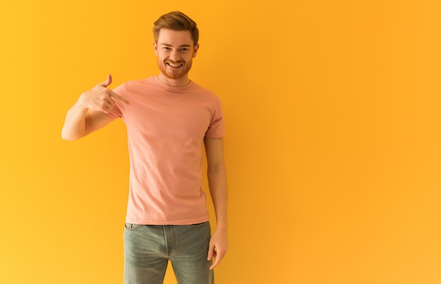 Young redhead man person pointing by hand to a shirt copy space, proud and confident