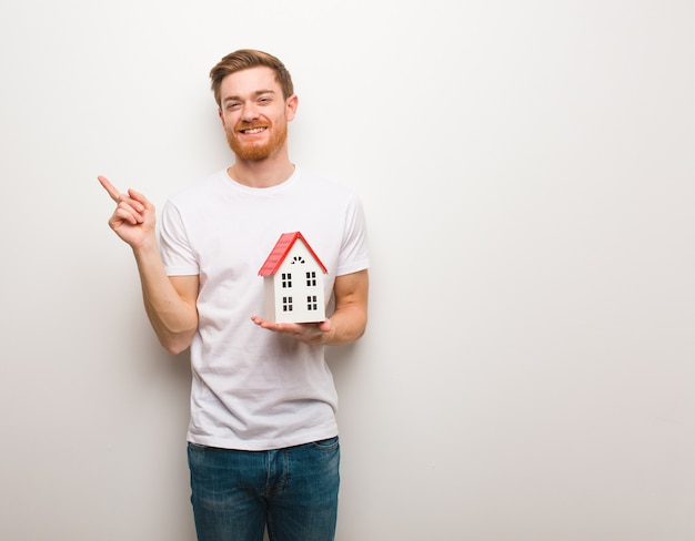 Young redhead man pointing to the side with finger. holding a house model.