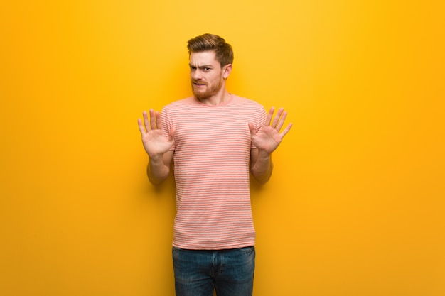 Young redhead man rejecting something doing a gesture of disgust