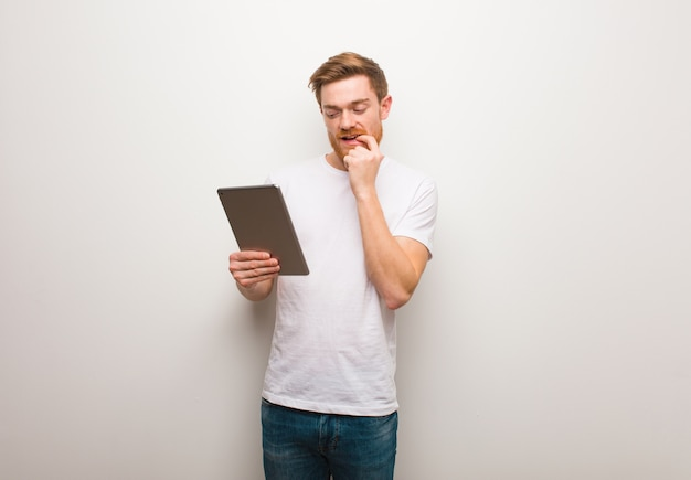 Young redhead man relaxed thinking about something and holding a tablet