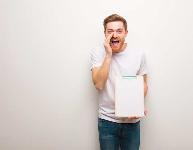 Young redhead man shouting something happy to the front. he is holding a clipboard.