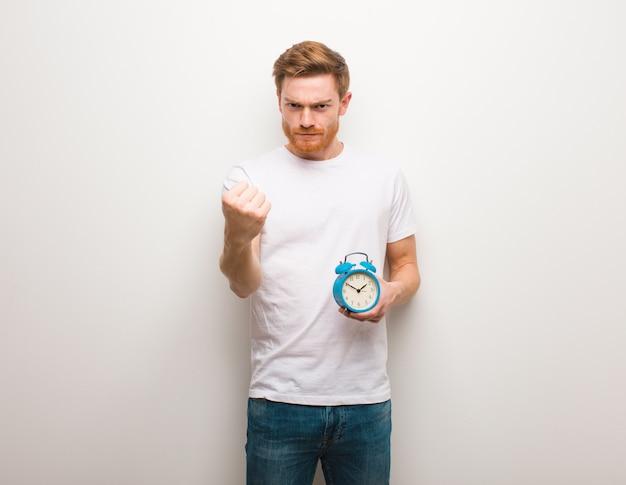 赤毛の若い男が拳を前に、怒りの表情を見せて彼は目覚まし時計を持っています。