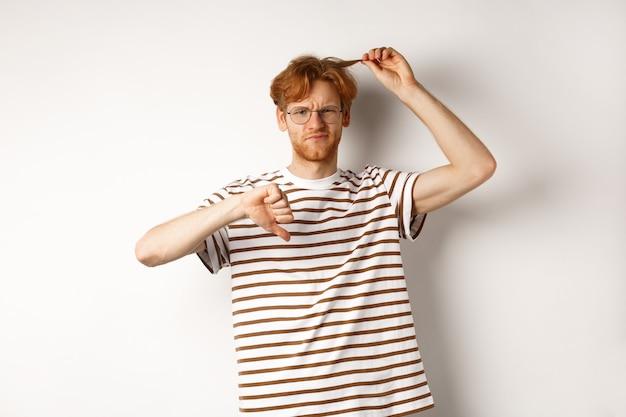 彼の厄介なヘアカットと親指を下に見せている若い赤毛の男は、白い背景の上に立って、美容院が必要です。