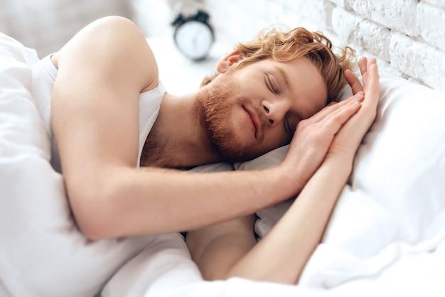 Молодой рыжий мужчина спит под белым одеялом.