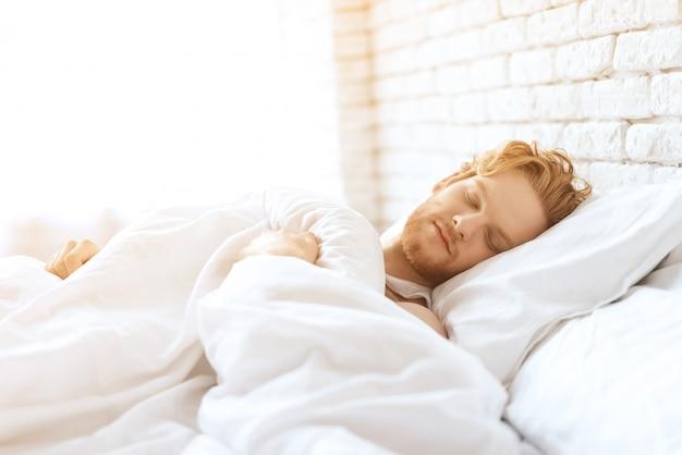 Young redhead man sleeps under white blanket.