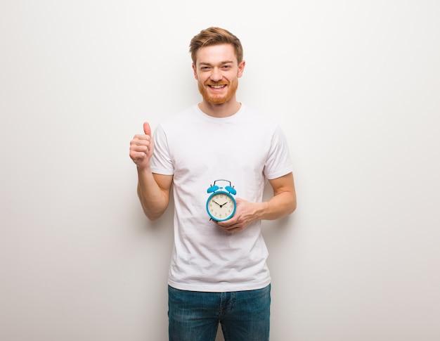 笑顔と親指を上げる若い赤毛の男。彼は目覚まし時計を持っています。
