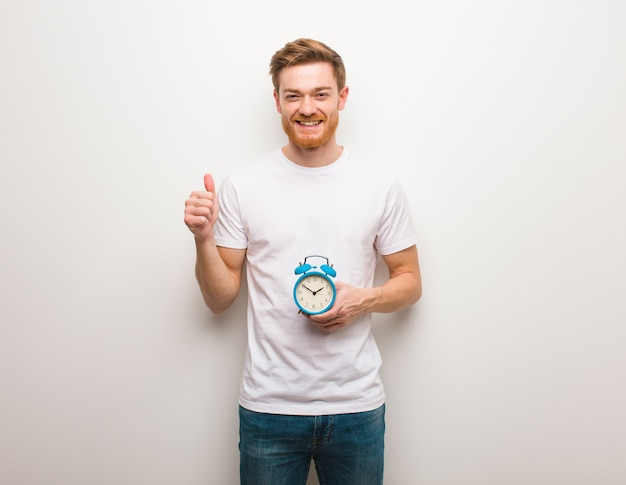 Young redhead man smiling and raising thumb up. he is holding an alarm clock.