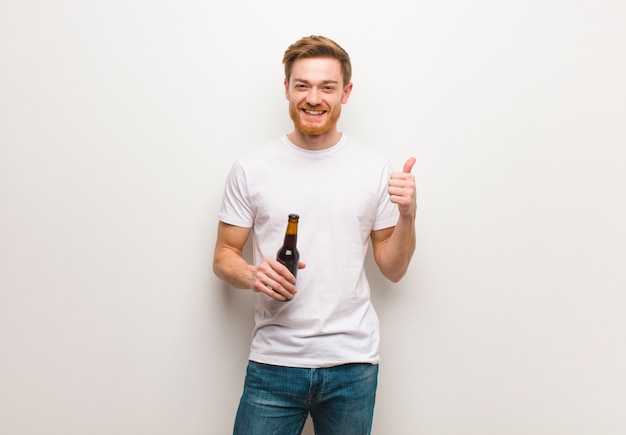 Young redhead man smiling and raising thumb up. holding a beer.