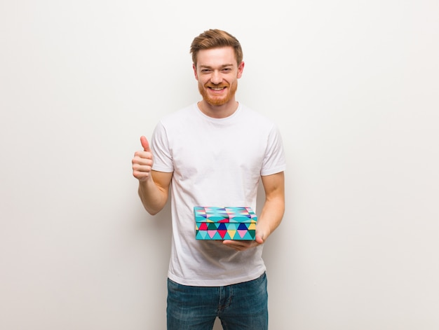 Young redhead man smiling and raising thumb up holding a gift box.