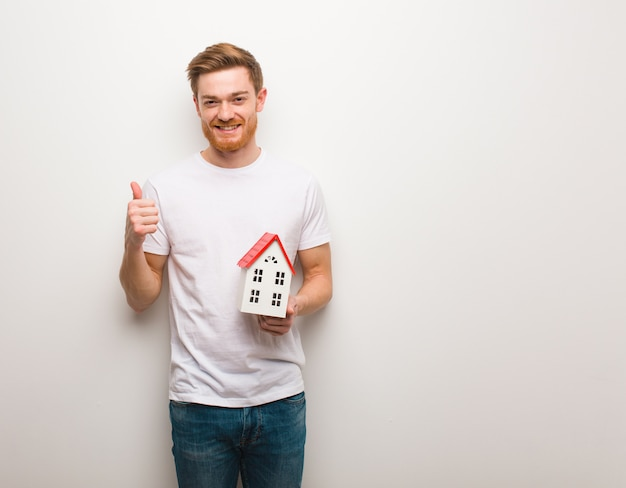 Young redhead man smiling and raising thumb up. holding a house model.