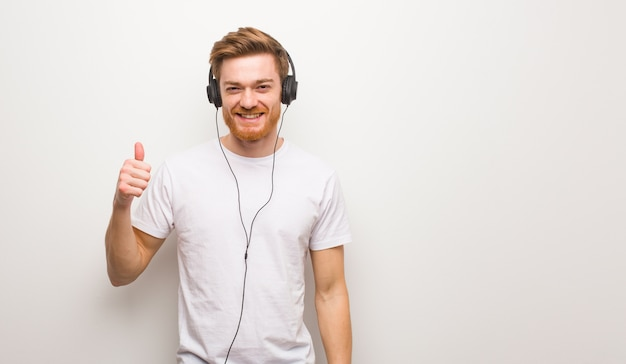 Young redhead man smiling and raising thumb up. listening to music with headphones.
