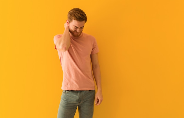 Young redhead man suffering neck pain