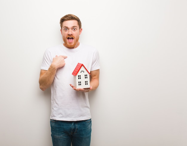 Young redhead man surprised, feels successful and prosperous. holding a house model.
