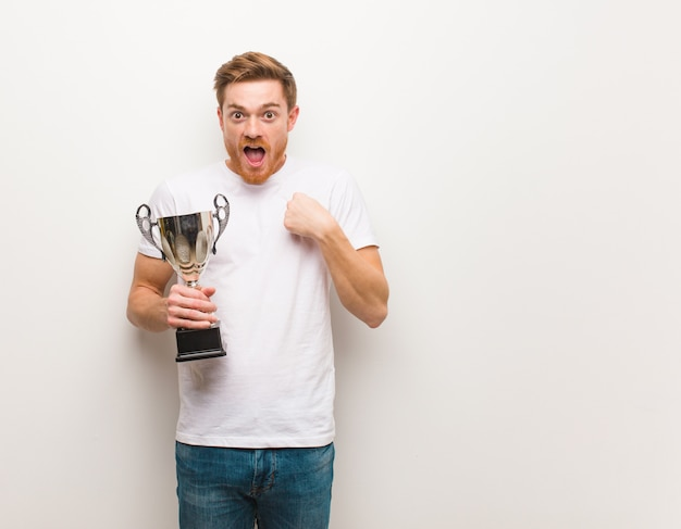 Young redhead man surprised, feels successful and prosperous. holding a trophy.