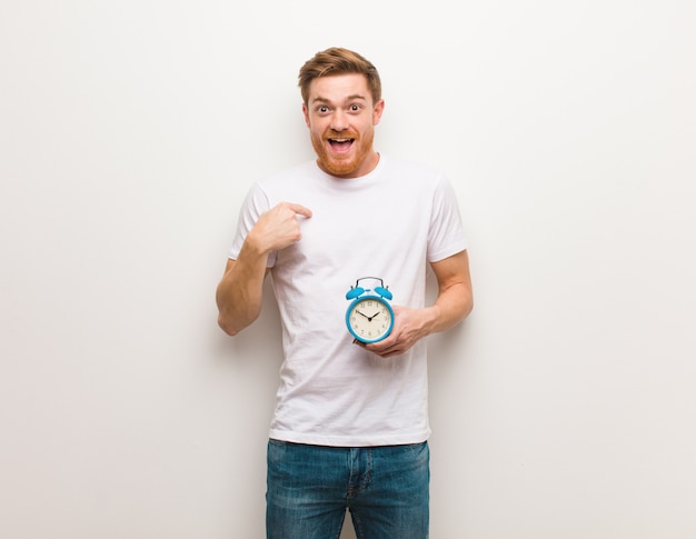 Young redhead man surprised, feels successful and prosperous