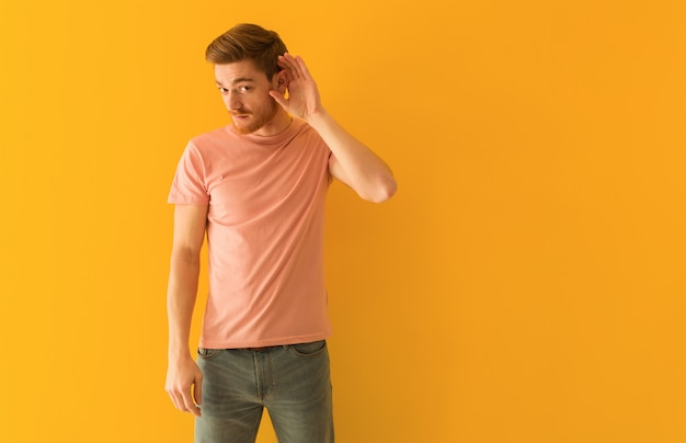 Young redhead man try to listening a gossip