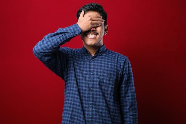 Молодой рыжий мужчина в повседневной рубашке улыбается и смеется с рукой на лице, прикрывая глаза от удивления. слепая концепция на красном фоне