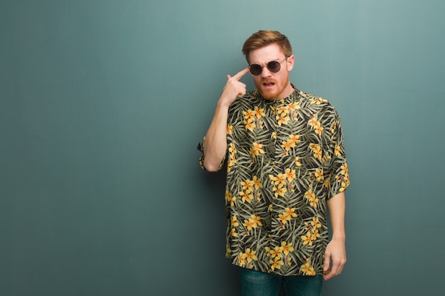Young redhead man wearing exotic summer clothes doing a disappointment gesture with finger
