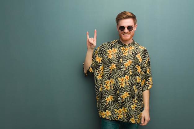 Young redhead man wearing exotic summer clothes doing a rock gesture