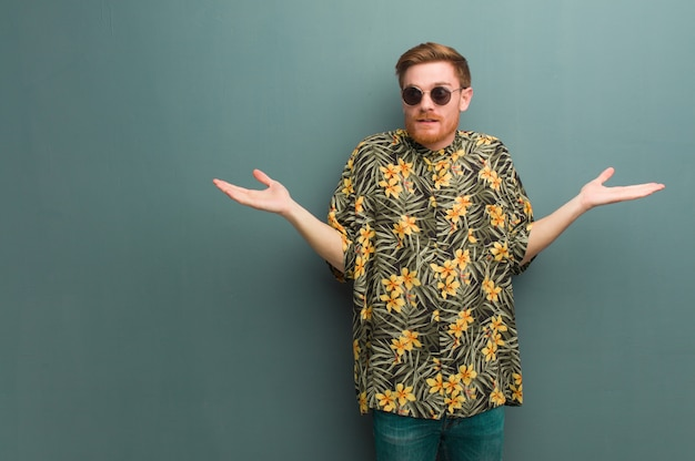 Young redhead man wearing exotic summer clothes doubting and shrugging shoulders
