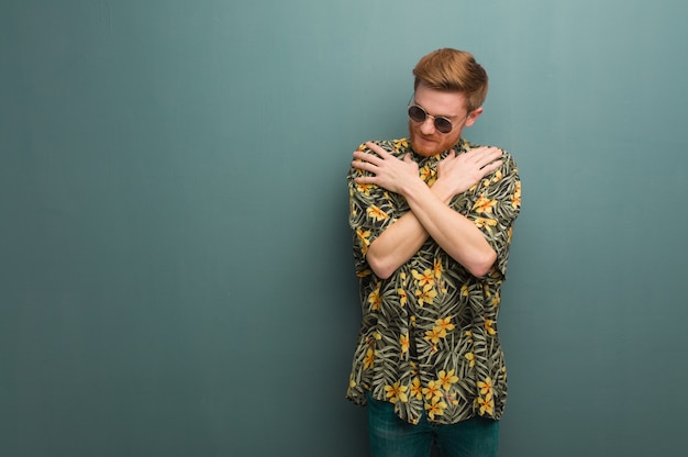 Young redhead man wearing exotic summer clothes giving a hug