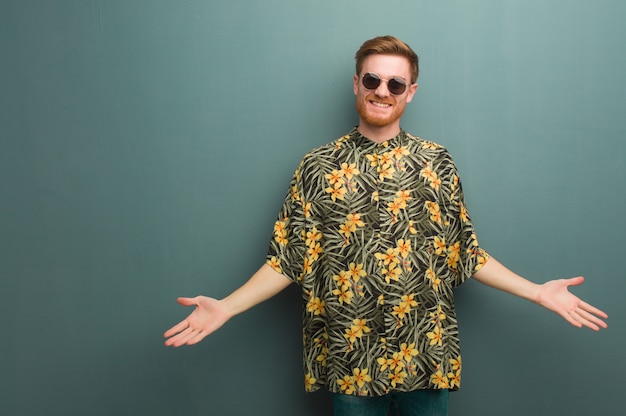 Young redhead man wearing exotic summer clothes inviting to come