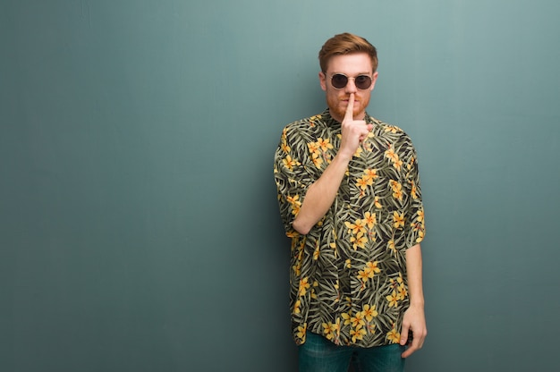 Young redhead man wearing exotic summer clothes keeping a secret or asking for silence