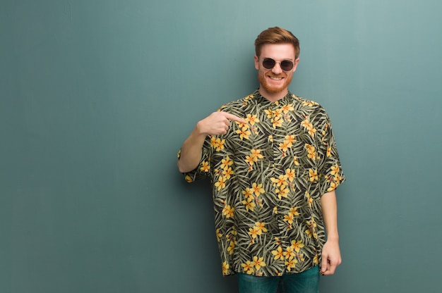 Young redhead man wearing exotic summer clothes person pointing by hand to a shirt copy space, proud and confident