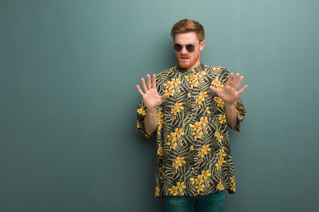 Young redhead man wearing exotic summer clothes rejecting something doing a gesture of disgust
