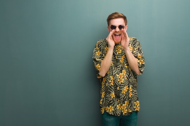 Young redhead man wearing exotic summer clothes shouting something happy to the front