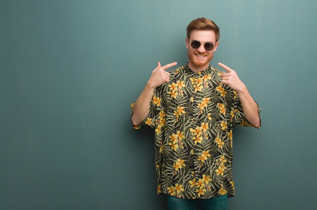 Young redhead man wearing exotic summer clothes smiles, pointing mouth
