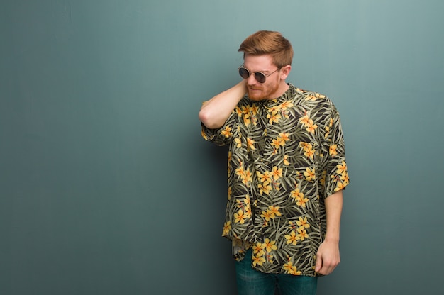 Young redhead man wearing exotic summer clothes suffering neck pain