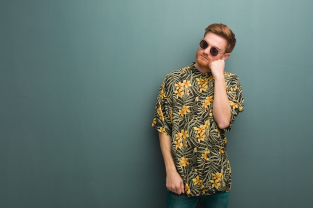 Young redhead man wearing exotic summer clothes thinking of something, looking to the side