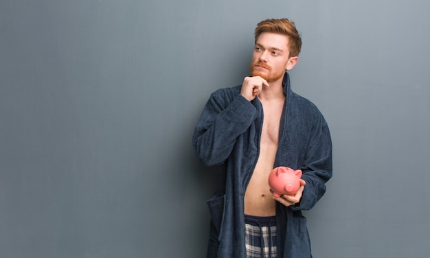 Young redhead man wearing pajama doubting and confused. he is holding a piggy bank.