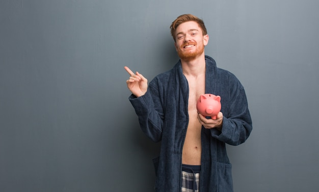 Young redhead man wearing pajama pointing to the side with finger. he is holding a piggy bank.