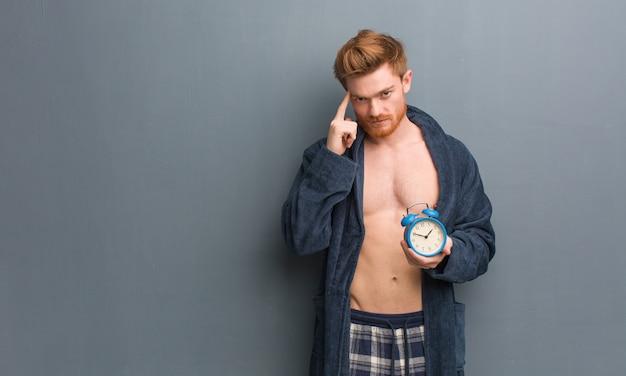 アイデアについて考えてパジャマを着ている若い赤毛の男。彼は目覚まし時計を持っています。