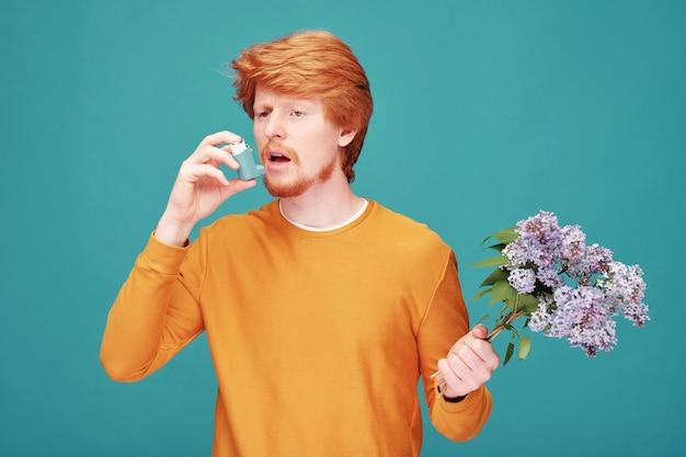 Молодой рыжий мужчина с бородой, страдающий астмой, использует ингалятор и держит сиреневые веточки на синем