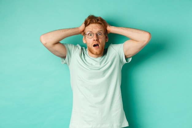 Young redhead man with beard, wearing glasses and t-shirt, holding hands on head and staring in panic, standing alarmed and anxious against turquoise background.
