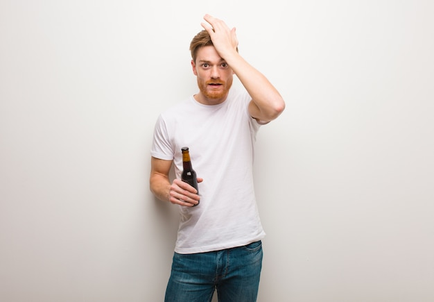 Young redhead man worried and overwhelmed. holding a beer.