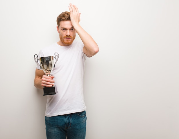 Young redhead man worried and overwhelmed. holding a trophy.