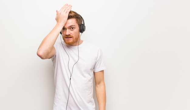 Young redhead man worried and overwhelmed. listening music with headphones.