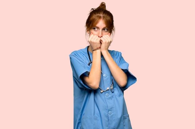 若い赤毛の看護師は少し緊張し、ピンクの背景の上に口に手を入れて怖い
