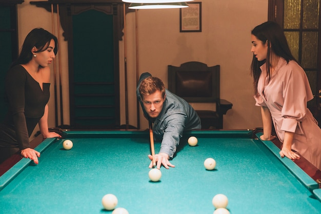 Young redhead player stand between two models. he aims into billiard ball. young women stand and look at gamel. they lean to table.