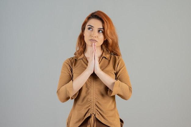 Young redhead praying and looking away on grey wall